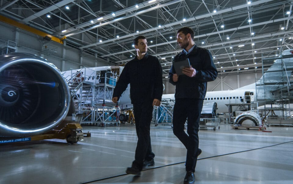 Two workers in airplane manufacturing facility