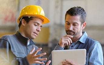 Two Workers Looking at Blueprint